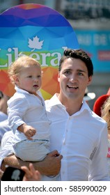 MONTREAL QUEBEC CANADA AUGUST 16 2015: Justin Trudeau hold a baby during the Montreal gay pride. Justin Pierre James Trudeau MP is a Canadian politician and the leader of the Liberal Party of Canada