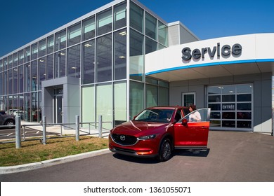 Montreal, Quebec, Canada August 31, 2018: Young male consultant and customer review a new car at a car dealership. Concept for car sale, Mazda Motor Show in Montreal, Canada.