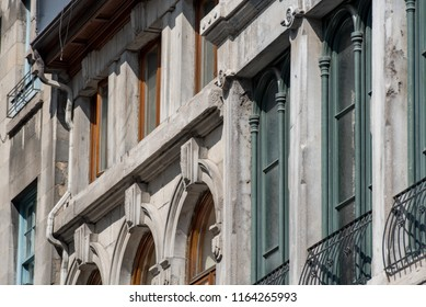 Montreal, Quebec, Canada.  Closeup of concrete buildings with brown, green, and teal window panes along Saint Paul Street West in Old Montreal, oblique view.