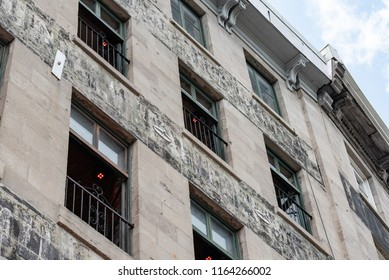 Montreal, Quebec, Canada.  Concrete building with green window frames and black security bars along Rue de la Commune East in Old Montreal, oblique view.