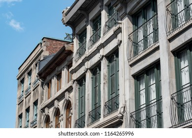 Montreal, Quebec, Canada.  Concrete buildings with brown, green, and teal window panes along Saint Paul Street West in Old Montreal, oblique view.