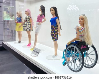 Montreal, Quebec Canada - December 16 2020: fashion dolls and toys in showcase of a local shopping mall, diversity of bodies and racial features, and a doll in a wheelchair with disability.