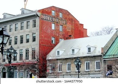 Montreal, Quebec / Canada - December 8 2020: colorful houses in Old Montreal, the Old Port area with historical buildings and touristic attractions. A hotel with red wall and old advertisement.