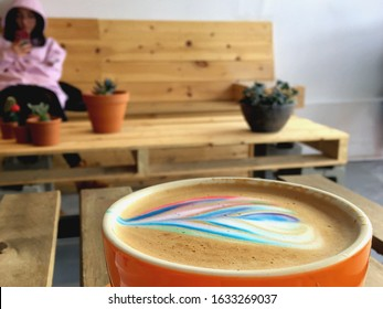 Montreal, Quebec / Canada - February 1 2020: Cozy neighborhood cafe Le VSL in Saint Laurent neighborhood, wooden furniture and succulent plant decor. A cup of latte, rainbow art. Girl is on her phone.