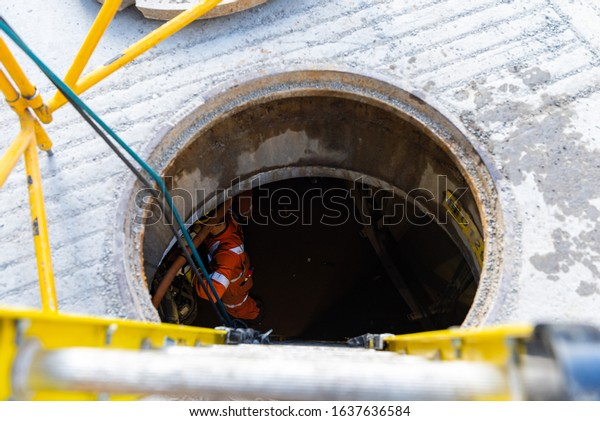 Montreal Quebec Canada February 5 2020: Looking down a Manhole opened with ladder going down and workers at the bottom