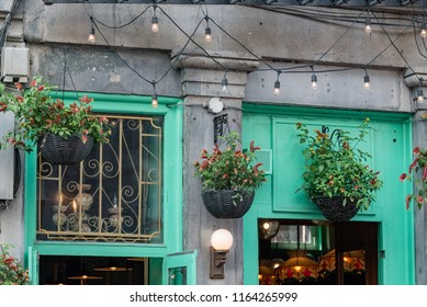 Montreal, Quebec, Canada.  Hanging flower baskets above a concrete building entrance with jade green wood doors and windows along Saint Paul Street West in Old Montreal.