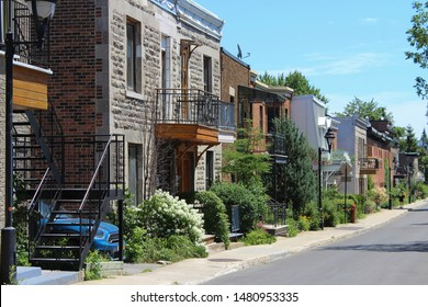 Montreal, Quebec / Canada - Jult 18 2019: perspective of a cozy street on Plateau Mont Royal with cute little houses and with cars parked along the curb.