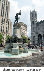Montreal, Quebec, Canada - July 10, 2018:  Maisonneuve Monument in the middle of Place D'Armes in Old Montreal, Notre-Dame Basilica in right background, vertical orientation.