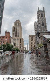 Montreal, Quebec, Canada - July 10, 2018:  Looking east down Notre-Dame Street West after a rain shower toward Notre-Dame Basilica on right, across from Place D'Armes, in Old Montreal.