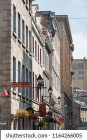 Montreal, Quebec, Canada - July 10, 2018:  Hanging flower baskets and shop signs along Saint Paul Street West at Saint Francois Xavier Street in Old Montreal, vertical orientation.