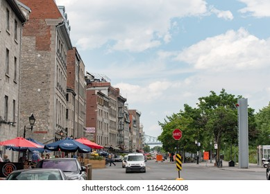 Montreal, Quebec, Canada - July 10, 2018:  Looking east down Rue de la Commune East near Saint Laurent Boulevard at people and buildings in Old Montreal.