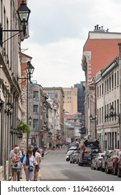 Montreal, Quebec, Canada - July 10, 2018:  Looking west down Saint Paul Street West toward Royal Square at people and buildings in Old Montreal, vertical orientation.