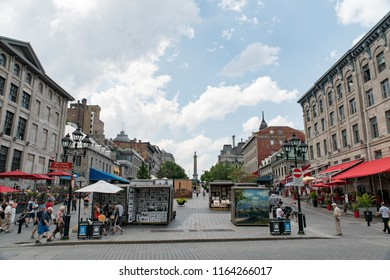 Montreal, Quebec, Canada - July 10, 2018:  People, buildings, and displays at Jacques Cartier Square in Old Montreal as viewed from Saint Paul Street East, Nelson's Column in center background.