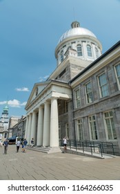 Montreal, Quebec, Canada - July 10, 2018:  People in front of Bonsecours Market along Saint Paul Street East in Old Montreal, vertical orientation, oblique view.