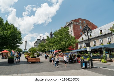 Montreal, Quebec, Canada - July 10, 2018:  People, buildings, and displays at Jacques Cartier Square in Old Montreal, Nelson's Column in left background.