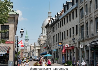 Montreal, Quebec, Canada - July 10, 2018:  Looking east down Saint Paul Street East toward the dome of Bonsecours Market and at people and buildings from Jacques Cartier Square in Old Montreal.