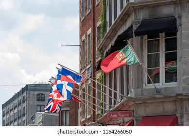 Montreal, Quebec, Canada - July 10, 2018:  Looking west at flags flying from a brown brick building on Saint Paul Street East at Saint Vincent Street in Old Montreal.