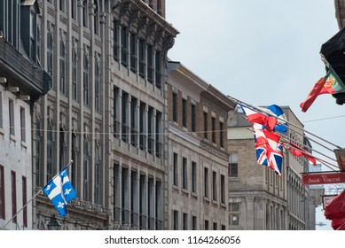 Montreal, Quebec, Canada - July 10, 2018:  Looking west down Saint Paul Street East at Saint Vincent Street at flags flying against a backdrop of buildings in Old Montreal.