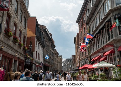Montreal, Quebec, Canada - July 10, 2018:  Looking west down Saint Paul Street East at Saint Vincent Street at people and buildings with flags in Old Montreal.