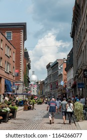 Montreal, Quebec, Canada - July 10, 2018:  Looking east down Saint Paul Street East at Saint Gabriel Street at people and buildings with flags in Old Montreal, vertical orientation.