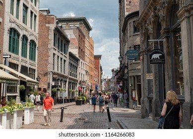 Montreal, Quebec, Canada - July 10, 2018:  Looking east down Saint Paul Street East near Saint Jean Baptiste Street at people and buildings in Old Montreal.