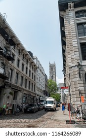 Montreal, Quebec, Canada - July 10, 2018:  Looking up Saint Sulpice Street from Saint Paul Street West toward Notre-Dame Basilica in middle background in Old Montreal, vertical orientation.