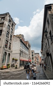 Montreal, Quebec, Canada - July 10, 2018:  Looking east down Saint Paul Street West at Marie-Morin Street at people and buildings in Old Montreal, vertical orientation.