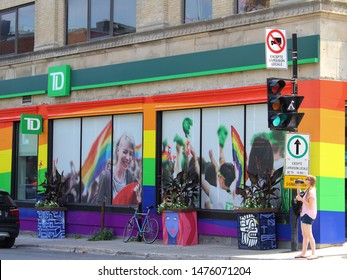 Montreal, Quebec / Canada - July 28 2019: a girl drinks from the bottle on a hot summer day in front of the facade of TD Bank in Gay Village decorated with rainbow Pride flags and LGBT pride photos.