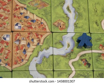 Montreal, Quebec / Canada - July 3 2019: the tiles and meeples of tabletop boardgame Carcassonne with a roads and castles, a popular family hobby.