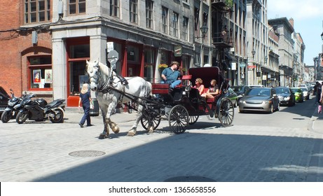 Montreal, Quebec, Canada, July 31, 2013: A horse-drawn carriage or caleche with tourists onboard in Old Montreal, Quebec.
