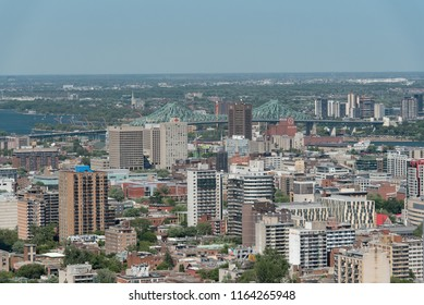Montreal, Quebec, Canada - July 9, 2018:  View looking northeast from Mount Royal Chalet lookout in Mount Royal Park across downtown toward Jacques-Cartier Bridge and Longueuil.