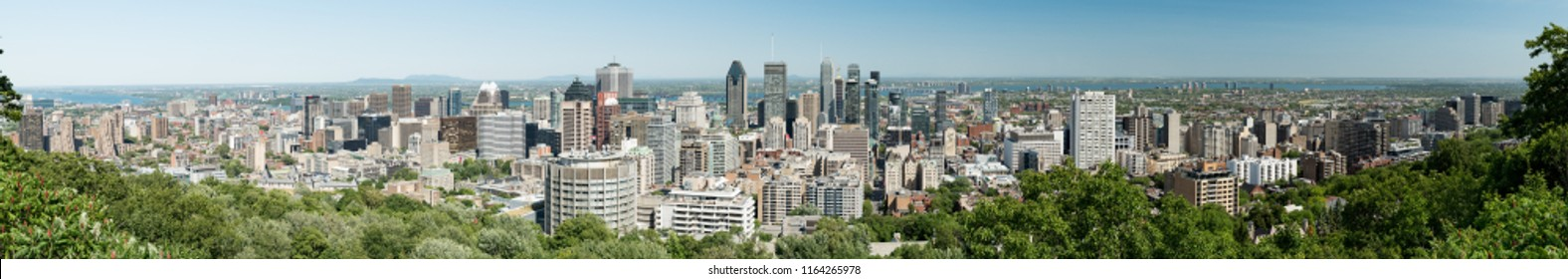Montreal, Quebec, Canada - July 9, 2018:  Panoramic view of downtown looking southeast from Mount Royal Chalet lookout in Mount Royal Park.