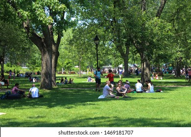 Montreal, Quebec / Canada - June 23 2019: parc Sir Wilfrid Laurier in the center of the city, Plateau Mont Royal neighborhood, with people relaxing on grass under the trees.