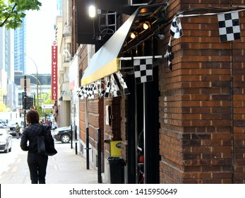 Montreal, Quebec / Canada - June 4 2019: a girl is going past a restaurant in city downtown that is decorated by checkered flags before car race Formula One Montreal.