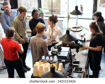 Montreal, Quebec / Canada - June 7 2019: the interior of a trendy hipster cafe Paquebot in the Old Montreal center with people waiting in line and barista preparing drinks.