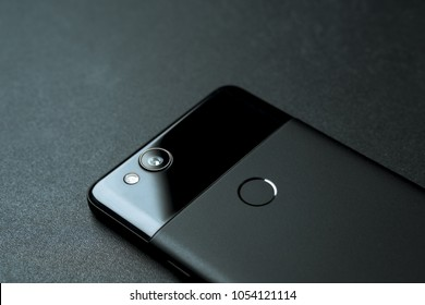 Montreal, Quebec / Canada - March 25 2018: Backside view of a black Google Pixel 2. The smartphone is laying flat on a black mousepad background. The phone camera features a 12MB sensor and f/1.8 lens
