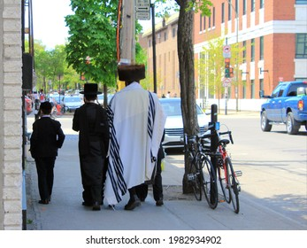 Montreal, Quebec Canada - May 15 2021: members of the religious Hassidic Jews community in Outremont neighborhood wearing traditional clothes in the street. A man in fur hat and two boys.
