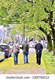 Montreal, Quebec / Canada - May 18th 2014: Trio of men strolling the leafy streets of Montreal in the Spring.