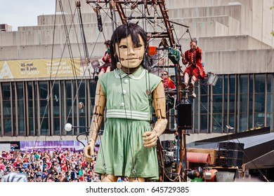 Montreal, Quebec, Canada - May 21, 2017: Place des Festivals - open-air event space. Little girl giant at the Giant marionettes of the Royal de Luxe (les Geants) event for 375 anniversary of Montreal.