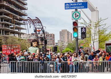 Montreal, Quebec, Canada - May 21, 2017: Place des Festivals - open-air event space. Sleeping little girl giant marionette and the crowd at event for 375 anniversary of Montreal.