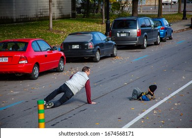 Montreal, Quebec / Canada - October 16 2010: Adult Man with a Child Wearing a Blue Jacket are Lying in the Middle of the Street