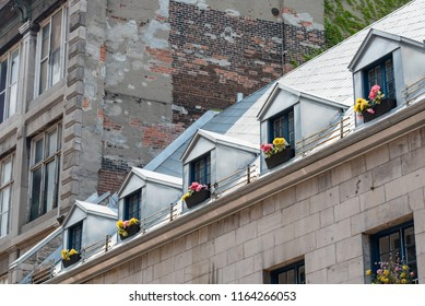 Montreal, Quebec, Canada.  Old windows with brown wicker flower baskets and blue painted wooden panes on a gray brick building with metal roof on Saint Paul Street East in Old Montreal, oblique view.