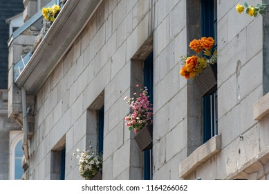 Montreal, Quebec, Canada.  Old windows with brown wicker flower baskets and blue painted wooden panes on a gray brick building along Saint Paul Street East in Old Montreal, oblique view.