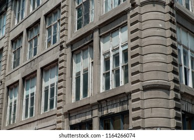 Montreal, Quebec, Canada.  Old wooden window panes with white peeling paint on a stone building on Saint Paul Street East in Old Montreal.