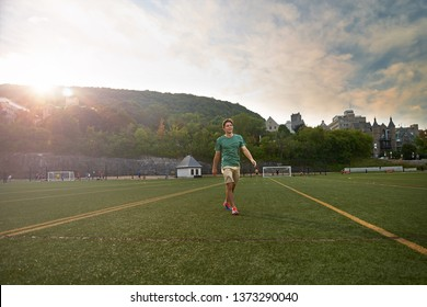 Montreal, Quebec, Canada, September 1, 2018: football field of McGill University. The guy in shorts and a T-shirt on the field at sunset. Sports for a young player.