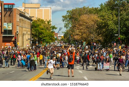 Montreal, Quebec Canada - September 27 2019: Sea of People Walking on Mont-Royal Street During March for Climate Demonstration, Man Taking picture with Phone and Young Boy Running in Foreground