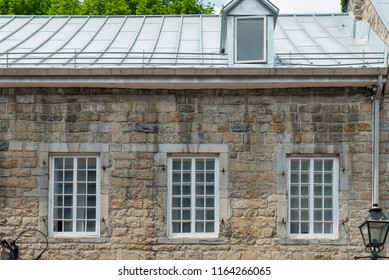 Montreal, Quebec, Canada.  Three old windows with white painted wooden panes on a stone building with metal roof on Saint Paul Street East in Old Montreal.