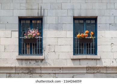 Montreal, Quebec, Canada.  Two old windows with brown wicker flower baskets and blue painted wooden panes on a gray brick building on Saint Paul Street East in Old Montreal.