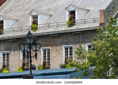 Montreal, Quebec, Canada.  Windows with brown wooden flower baskets and white panes on a gray brick building with metal roof along Jacques Cartier Square in Old Montreal, oblique view.