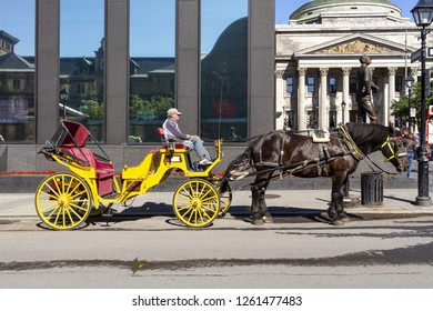 Montreal, Quebec, June 25, 2018 - Caleche drawn by horse and Rider waiting for a fare in Old Montreal.